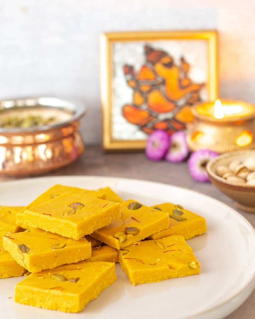 mango barfi on a plate with Ganesh photo in the back