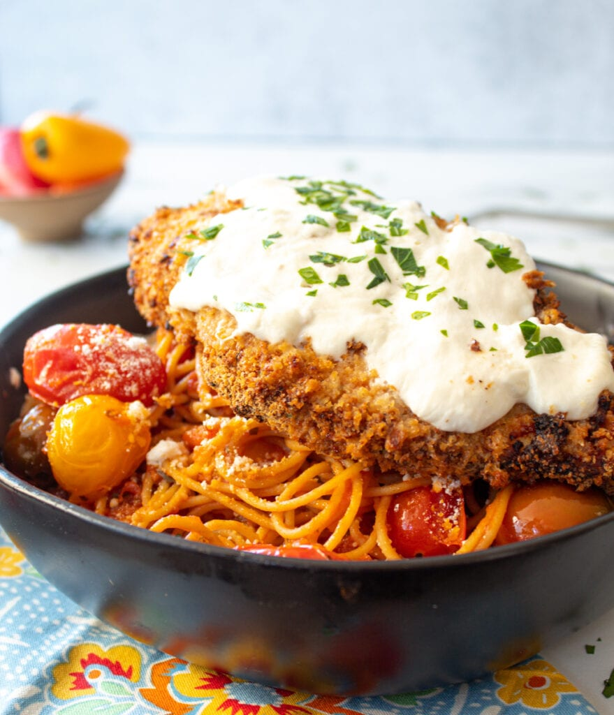 Air Fryer Spicy Chicken Parmesan on an angle topped on a bowl of pasta