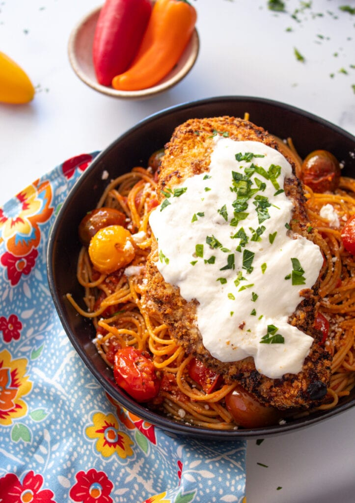 Air Fryer Spicy Chicken Parmesan on bowl with pasta and peppers
