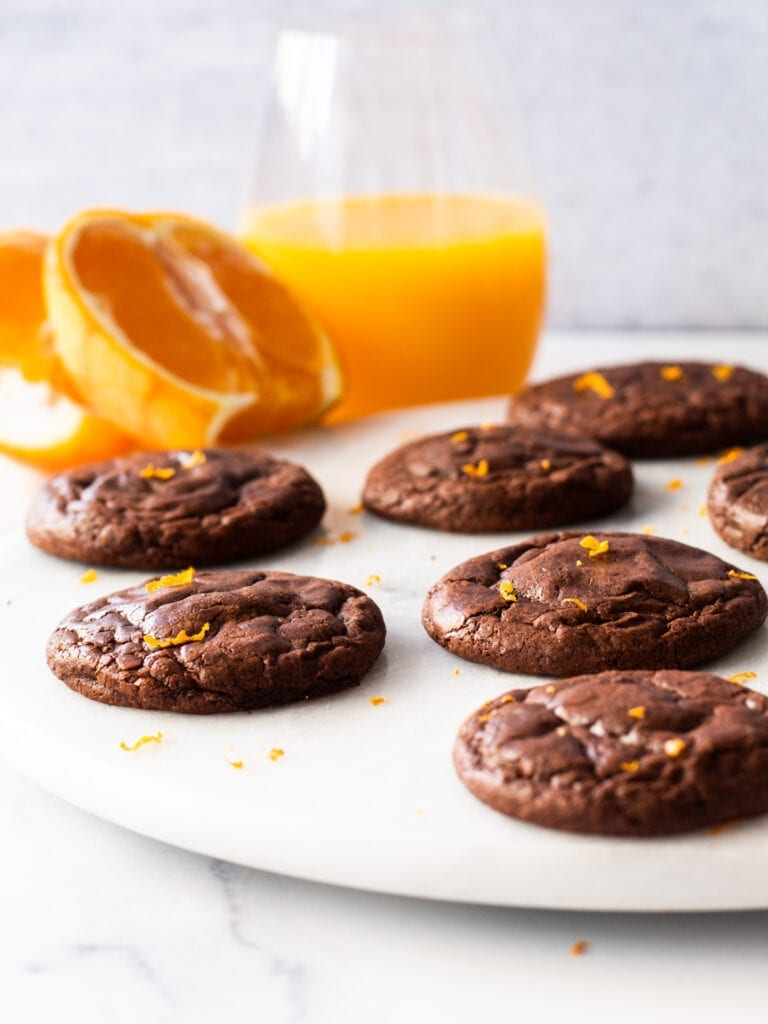chocolate cookies on a plate with orange and juice in the background