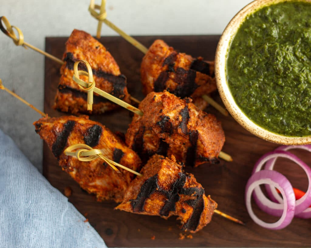 Skewered chicken tikka with mint chuntey in a bowl in the