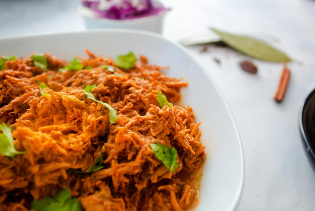 shredded chicken in a bowl with spices in the background