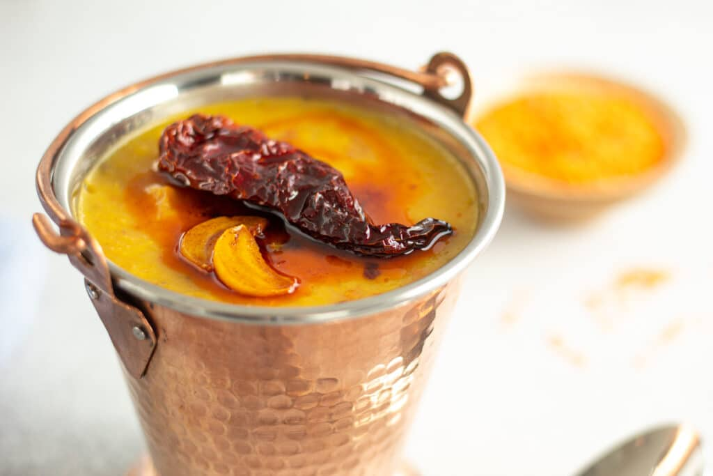 bucket of daal with tadka and chili on top